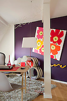 This home office is furnished with a quirky collection of pieces which includes a hanging lamp and a  modular bookshelf
