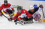 Sochi, RUSSIA - Mar 13 2014 - Tyler McGregor protects the puck as Canada takes on USA in Sledge Hockey Semi-Final at the 2014 Paralympic Winter Games in Sochi, Russia.  (Photo: Matthew Murnaghan/Canadian Paralympic Committee)