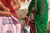 Amritsar, Punjab, India. Two women, their hands painted with intricate henna designs. One holds a pink plastic bag with 'Welcome' in English and Punjabi writing.
