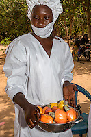 Farm Worker with Bowl of Cashew Apples Ready for Slicing.  The Gambia