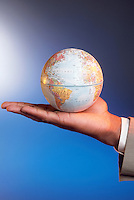 An African American man holds a globe in the palm of his hand.