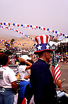 The Fourth of July Parade in Cayucos Beach, California turns the tiny town into the biggest city on the Central Coast for one day every year.  Man dressed as Uncle Sam watches parade.