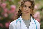 Portrait of a young woman medical student with contemplative thoughtful look, considering a career in natural medicine, healthcare, doctor, physician. Wearing a lab coat in natural outdoor settings in a garden with beautiful blossoming flowers