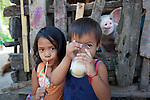 A young girl and boy drink milk outdoors with the family pig, in the village of Corong Corong, near El Nido, the gateway to the Bacuit Archipelago in Palawan, Philippines.