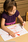Preschool 3 year olds art activity girl drawing with marker using left hand