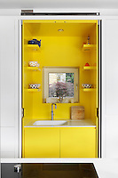 A white kitchen cupboard with doors that fold back conceals a sink in a vibrant yellow recess with a window to the garden