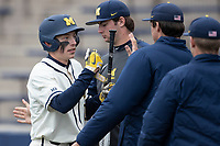 Michigan Wolverines third baseman Blake Nelson (10) is greeted after scoring against the Indiana State Sycamores on April 10, 2019 in the NCAA baseball game at Ray Fisher Stadium in Ann Arbor, Michigan. Michigan defeated Indiana State 6-4. (Andrew Woolley/Four Seam Images)