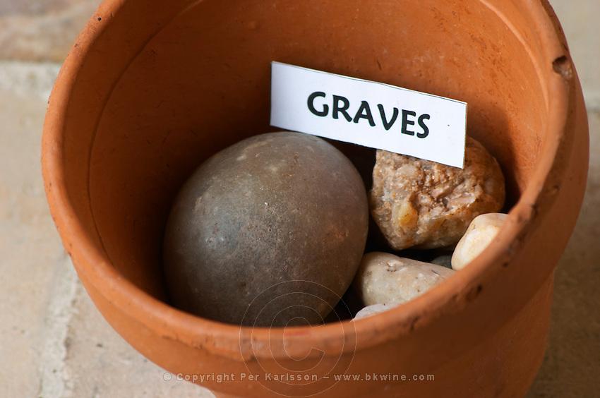 Plant pot with soil sample to illustrate different soil types, part of a series: stone rock pebble, graves Chateau Villerambert-Julien near Caunes-Minervois. Minervois. Languedoc. Terroir soil. France. Europe. Soil with stones rocks.