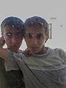 Iraq 2013 . Domiz Refugee Camp, two boys looking through the window of the barbershop.Irak 2013.Au camp de Domiz, 2 jeunes refugies regardant a travers la vitrine du coiffeur.
