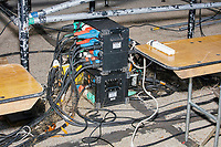 A box connected to many wires is seen under the press riser at a Make America Great Again Victory Rally in the final week before the Nov. 3 election at Pro Star Aviation in Londonderry, New Hampshire, on Sun., Oct. 25, 2020.