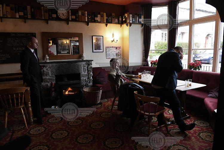 UKIP leader Nigel Farage, flanked by his personal security man and strategic advisor Chris Bruni-Lowe, takes a break from campaigning for the 7 May 2015 general election in The Coldstreamer public house, near Penzance, Cornwall.