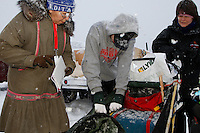 Barb Redington hands a packet of trail mail to Junior musher Jeff Holt Jr. just prior to the start of the 2009 Junior Iditarod on Knik Lake on Saturday Februrary 28, 2009.