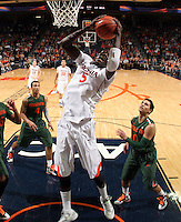 CHARLOTTESVILLE, VA- JANUARY 7: Assane Sene #5 of the Virginia Cavaliers reaches for the rebound in front of Miami Hurricane defenders during the game on January 7, 2012 at the John Paul Jones Arena in Charlottesville, Virginia. Virginia defeated Miami 52-51. (Photo by Andrew Shurtleff/Getty Images) *** Local Caption *** Assane Sene