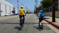 Holland, on his Yedoo kick scooter, and Michelle, on her Terry Burlington city bike, ride down Main Street near Sotello in Los Angeles during the 2017 (17th annual) Los Angeles River Ride.