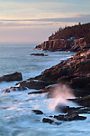 Morning sun illuminates the Otter Cliff and the rocky shoreline along Ocean Drive in Acadia National Park, Maine, USA