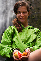 Close-up view of smiling woman holding a fresh guava fruit found along the trail to Hanakapiai Falls, Napali Coast, Kauai, Hawaii