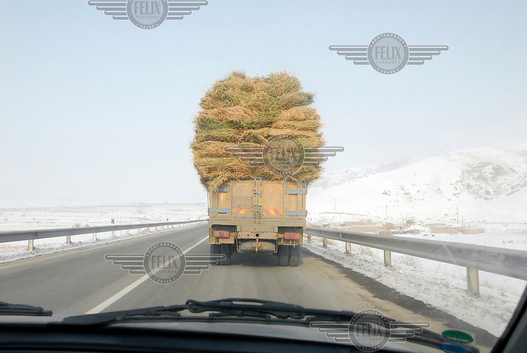 A truck loaded with hay drives along a road near the border between Iran and Armenia.