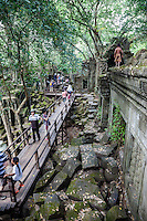 Cambodia, Beng Mealea, 12th. Century.  Tourists on Walkway through Sanctuary Ruins.