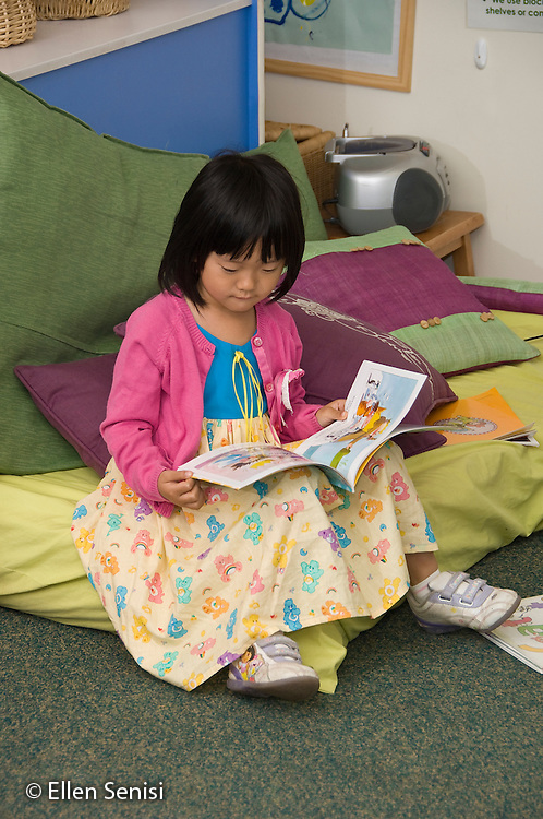 MR / College Park, Maryland.Center for Young Children, laboratory school within the College of Education at the University of Maryland. Full day developmental program of early childhood education for children of faculty, staff, and students at the university..Student (girl,5, Asian American) sits on pillows and reads books in classroom..MR: Liu1.© Ellen B. Senisi