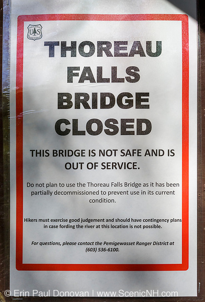"""May 23, 2018 - Thoreau Falls Trail bridge closed sign. The Thoreau Falls Trail bridge, which crosses the East Branch of the Pemigewasset River, in the Pemigewasset Wilderness is not safe and is out of service. The trail is still open, but hikers will have to ford the river at this location.<br /> <br /> The sign states: """"Do not plan to use the Thoreau Falls Trail bridge as it has been partially decommissioned to prevent use in its current condition. Hikers must exercise good judgment and should have contingency plans in case fording the river at this location is not possible."""""""
