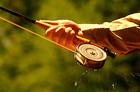 Water spins from a fishing reel on a fly rod grasped in a hand.