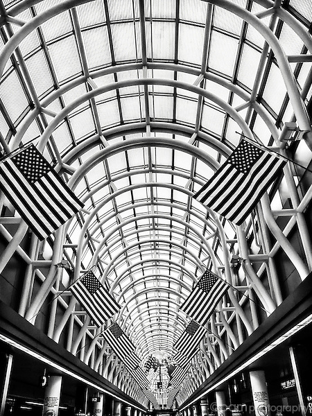 Black and white of arch in the Chicago O'Hare airport with American flags.