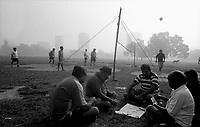 11.2003 Calcutta (West Bengal)<br /> <br />  Men playing cards and others playing volley ball in the Maidan garden.<br /> <br /> Hommes en train de jouer aux cartes et d'autres aux volley ball dans le jardin de Maidan.