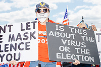 """A woman wears Trump 2020 campaign shirt, hat, and earrings, and a facemask reading """"Tastes like socialism"""" while holding signs reading """"Don't let the mask silence you"""" and """"Is this about the virus or the election"""" as people gather for an anti-lockdown protest organized by the alt-right group Super Happy Fun America near the home of Massachusetts governor Charlie Baker in Swampscott, Massachusetts, on Sat., May 16, 2020. The other side of the black sign read """"WWG1WGA / Q / #Obamagate"""" which are references to the QAnon conspiracy theories prevalent among fringe conservative circles. """"Obamagate"""" has recently been talked about by US President Donald Trump without reference to what the """"Obamagate"""" scandal might be. The protest was in defiance of Massachusetts orders mandating face coverings and social distancing and prohibiting gatherings larger than 10 people during the ongoing Coronavirus (COVID-19) global pandemic. The state's stay-at-home order is expected to be updated on May 18, 2020, with a phased reopening plan issued by the governor as COVID-19 cases continue to decrease. Anti-lockdown protests such as this have become a conservative cause and have been celebrated by US president Donald Trump. Many of the protestors displayed pro-Trump messages or wore Trump campaign hats and shirts with phrases including """"Trump 2020"""" and """"Keep America Great."""" Super Happy Fun America, organizers of the protest, are an alt-right organization best known for creating the 2019 Boston Straight Pride Parade."""