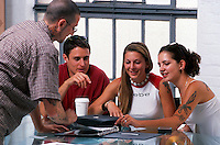 Young adults working together at a business meeting in a casual office setting.