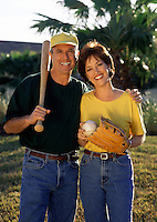 Portrait of an affectionate, smiling couple with softball equipment; bat, ball and glove.