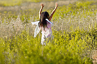 Young girl with fairy wings and arms outspread in a field of flowers