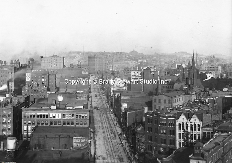 Pittsburgh PA: View of City from the top of the Empire Building. View of the city looking up Liberty Avenue towards the Pennsylvania Railroad Station. View of three sets of trolley tracks on Liberty Avenue. Company signs on city buildings included: C.A. Verner Shoes, Home Trust Company of Pittsburgh, JC Lindsay Hardware Company, JG Lauer Toys on Liberty Avenue, John Wallace Produce, Lyle Brothers Hardware on Liberty Avenue, Monongahela National Bank, New York Dentist on Liberty Avenue, Pennsylvania Railroad Station, and Renwick Brothers Wholesale Millinery