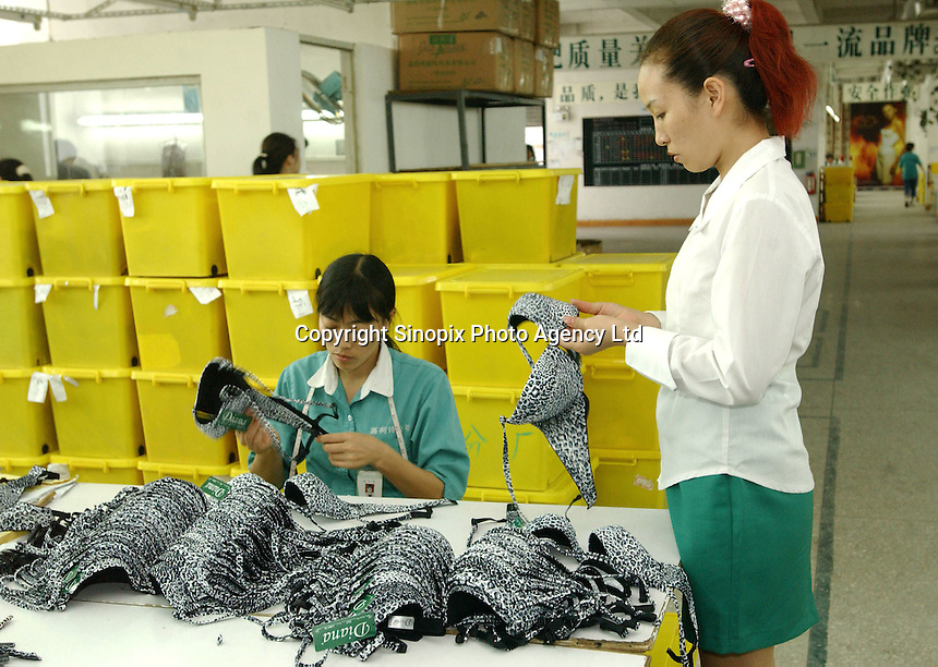 A line manager inspects work at the Jealousy factory at the International Underwear City, Yanbu Town, Nanhai District, Foshan City, Guangdong, China.  Jealousy produces 11 million bras annually and is increasing production by about 20 percent annually...PHOTO BY SINOPIX