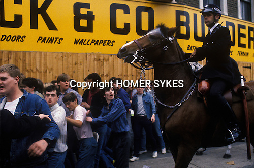 Chelsea Stamford Bridge football ground. Arsenal football fans after a game police crowd control on horseback. London. UK 1980s
