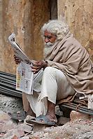 India, Rishikesh.  Bearded Old Man Reading a Hindi Newspaper.