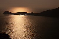 A small sailing boat sails between two Greek islands of Kalymnos and Telendos at sunset.