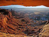 Washerwoman Arch and the Monster are visible in the background of this vew beneath Mesa Arch in Canyonlands National Park in Utah