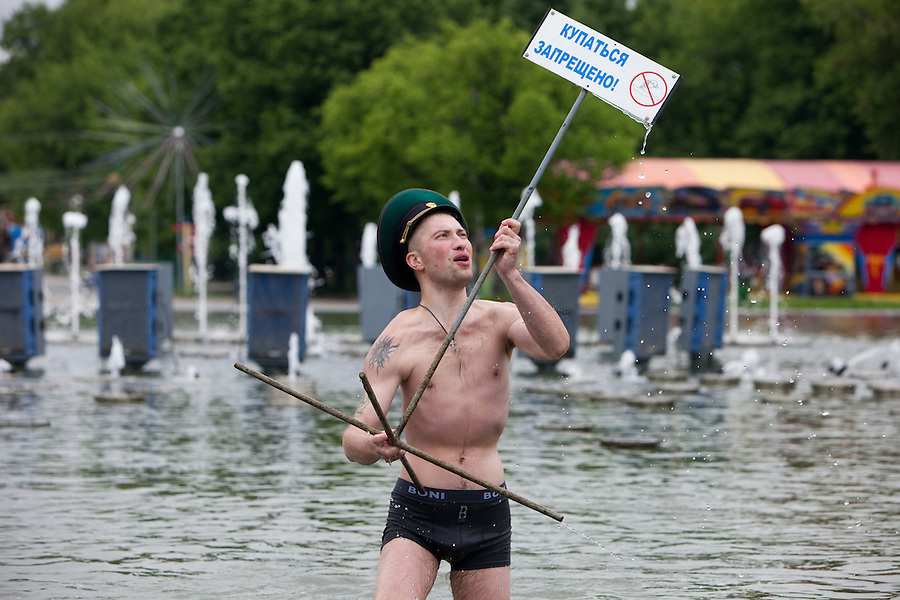 """Moscow, Russia, 28/05/2010..A member of the Russian Border Troops in a Gorky park lake waves a sign saying """"no swimming"""" as the regiment celebrated their annual holiday.."""