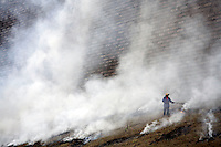 A worker burns trash and dried grass along the Yangtze River in Wanzhou District, Chongqing, China..19 Oct 2007