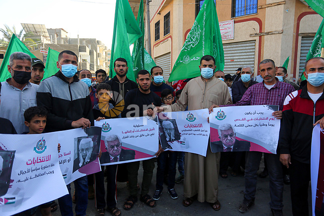 Palestinian supporters of Hamas movement demonstrate against postponement of the Palestinian parliamentary and presidential elections, calling for holding elections on planned date in Dair Al Balah in the central of Gaza Strip on April 30, 2021. Palestinian President Mahmoud Abbas announced early Friday that the legislative elections scheduled for May 22 will be postponed until further notice. Photo by Ashraf Amra