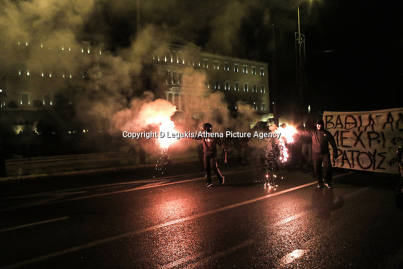 Pictured: Tuesday 02 December 2014<br /> Re: At least 15 people have been arrested after a peaceful support rally for jailed hunger strike anarchist turned into violent confrontation with police. Authorities used tear gas and stun grenades to quell rioters carrying Molotov cocktails.<br /> As an estimated between 8,000 and 10,000 protesters marched through the central Athens shouting slogans in support of Nikos Romanos, the imprisoned anarchist who is staging a hunger strike as he demands the right to be able to attend university, anarchists' march got violent on the streets of Exarchia, downtown Athens.