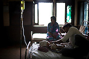 A young man is seen taking care of his ill child in in the pediatrics section of  Maharani Laxmibai Medical College in Jhansi, Uttar Pradesh, India. The Indian government spends $1.4 billion a year - on programs that include weighing newborn babies, counseling mothers on healthy eating and supplementing meals, but none of this is yeilding results. According to UNICEF, some 48% of Indian children, or 61 million kids, remain malnourished, the clinical condition of being so undernourished that their physical and mental growth are stunted. Photo: Sanjit Das/Panos for The Wall Street Journal.Slug: IMALNUT