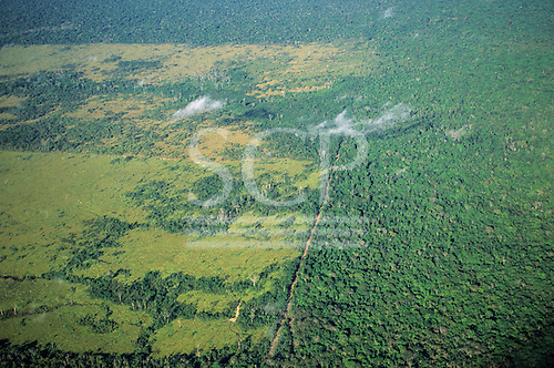 Amazonia, Brazil. Aerial view of Rainforest with large areas cleared for farming and cattle ranching; dirt road passing through ranch land.