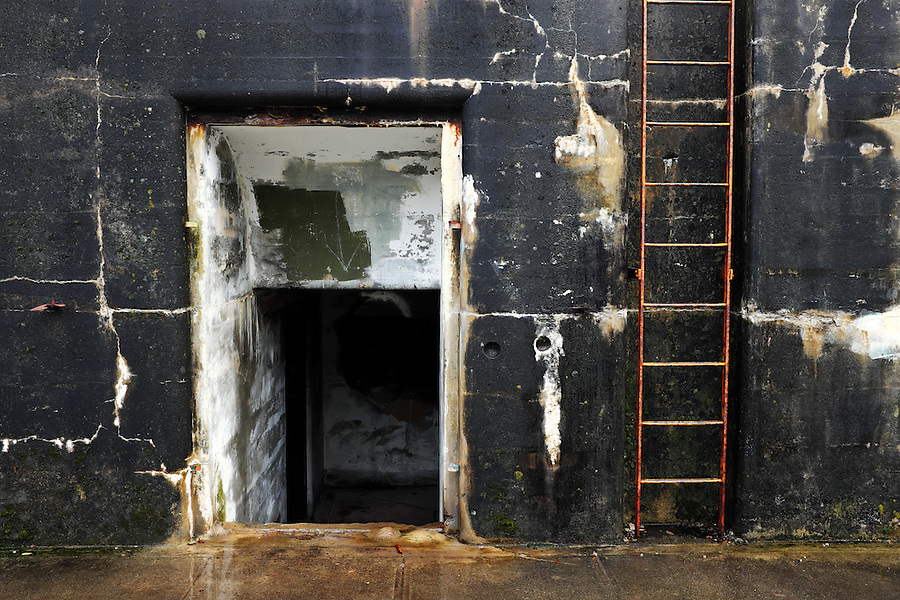 Rusty steel ladder and tunnel entry in moss and algae coverred concrete bunker wall, Artillery Hill, Fort Worden State Park, Port Townsend, Washington, USA