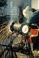 Pipe fitter grinding pipe in factory construction site