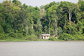 Pará State, Brazil. The Amazon River. Thatched wooden ribeirinho house with woman at the door.