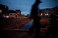.Aymara man walking at sunset in El Alto.Just 25 years ago it was a small group of houses around La Paz  airport, at an altitude of 12,000 feet. Now El Alto city  has  nearly one million people, surpassing even the capital of Bolivia, and it is the city of Latin America that grew faster .<br /> It is also a paradigmatic city of the tubles and traumas of the country. There got refugee thousands of miners that lost  their jobs in 90 ´s after the privatization and closure of many mines. The peasants expelled by the lack of land or low prices for their production. Also many who did not want to live in regions where coca  growers and the Army  faced with violence.<br /> In short, anyone who did not have anything at all and was looking for a place to survive ended up in El Alto.<br /> Today is an amazing city. Not only for its size. Also by showing how its inhabitants,the poorest of the poor in one of the poorest countries in Latin America, managed to get into society, to get some economic development, to replace their firs  cardboard houses with  new ones made with bricks ,  to trace its streets,  to raise their clubs, churches and schools for their children.