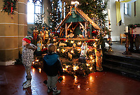 Oud Zevenaar-  Interieur van de Sint Martinuskerk. Kinderen staan bij een Kerststal tijdens  de Midwinterhoorntocht door Zevenaar
