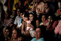 People watch a performance at the Jhon Danyer Circus. Around a dozen small circuses wander the poorer neighbourhoods around the city of Medellin putting on performances in what can be a hand to mouth existence. Despite falling audience numbers, new health and safety regulations and other bureaucracy these small family businesses, many of whom have existed for generations, still scrape a living in a world where the people are more accustomed to being entertained by soap operas than by live entertainment.