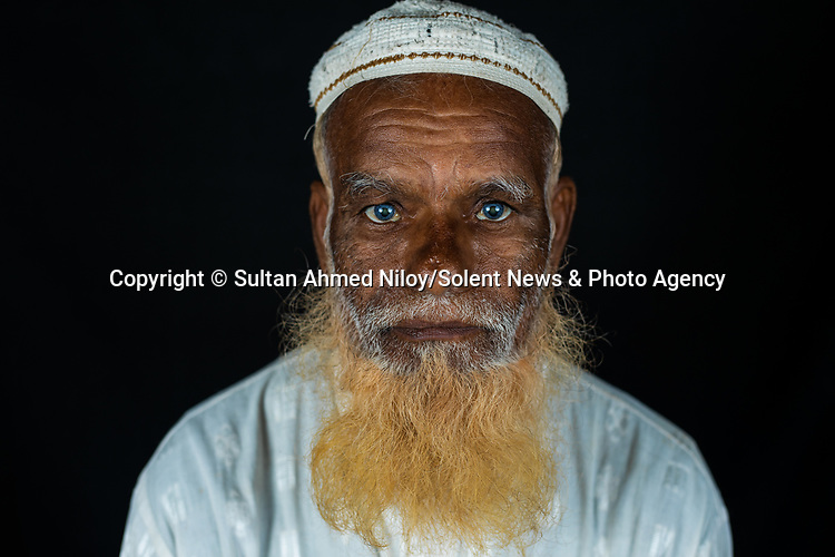 Pictured: Shukur Mia<br /> <br /> Family members with an unusual pigmentation show off their shockingly bright, blue eyes.  Eyes of this colour are rare for people of a darker skin tone, and the cause is a lack of melanin pigment in the iris of the eye.<br /> <br /> Lower levels of melanin are more commonly found in people with lighter skin tones, meaning they are more likely to have lighter coloured eyes.  The grandfather's name is Shukur Mia, who is photographed with his granddaughter Tasnim, 11, and grandson Mehedi, 6.  SEE OUR COPY FOR DETAILS.<br /> <br /> Please byline: Sultan Ahmed Niloy/Solent News<br /> <br /> © Sultan Ahmed Niloy/Solent News & Photo Agency<br /> UK +44 (0) 2380 458800